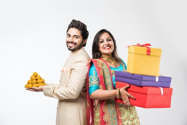 Indyjska para z pudełkami laddu i prezentów na diwali lub festiwalu, stojąc na białym tle nad białym tłem. noszenie tradycyjnych ubrań