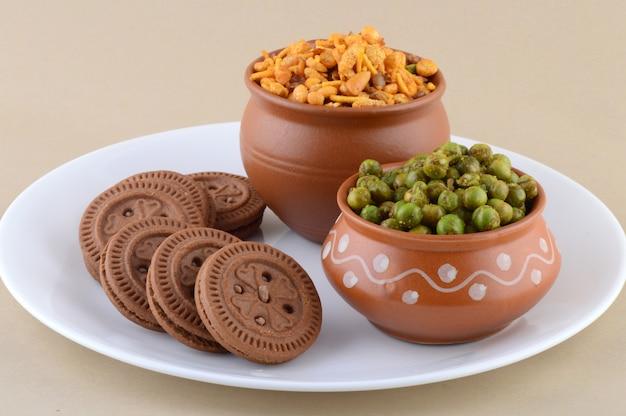 Indyjska przekąska: mieszanka, kremowe ciastko i przyprawiony smażony zielony groszek {chatpata matar} w talerzu.