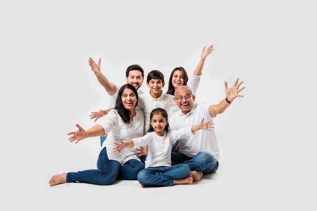 Indyjska rodzina azjatyckich siedzi na białym tle. starsza i młoda para z dziećmi na sobie biały top i niebieskie dżinsy. selektywne skupienie