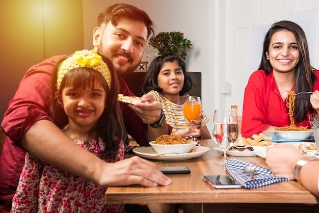 Indyjska rodzina jedząca jedzenie przy stole w domu lub w restauracji spożywająca wspólny posiłek