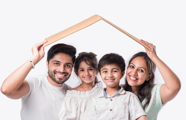 Indyjska rodzina ojciec, matka, syn i córka trzymają papierowy model domu 3d - real istate concept in india