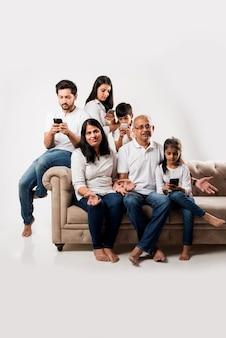Indyjska rodzina siedzi na kanapie, podczas gdy starsi dorośli się nudzą, a młodzi członkowie są zajęci smartfonem