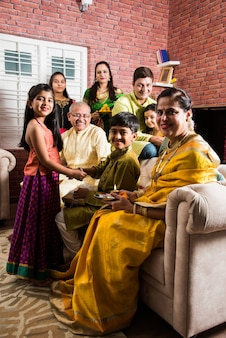Indyjska rodzina świętująca raksha bandhan lub festiwal rakhi w domu, ubrana w tradycyjne ubrania i siedząca nad sofą