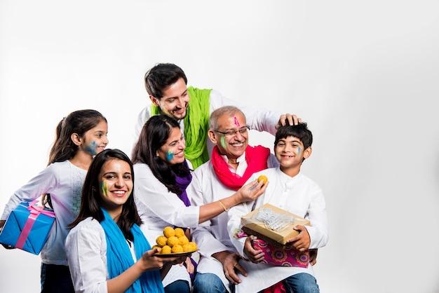 Indyjska rodzina świętująca święto holi ze słodkimi prezentami laddu i kolorami na talerzu