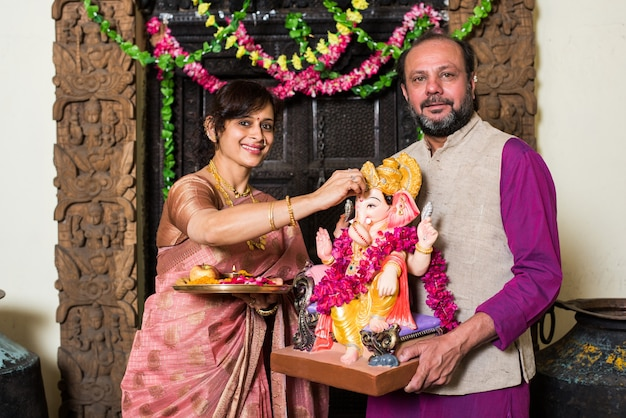 Indyjska rodzina świętuje ganeśćaturthi, wykonując ganpati puja lub poojan