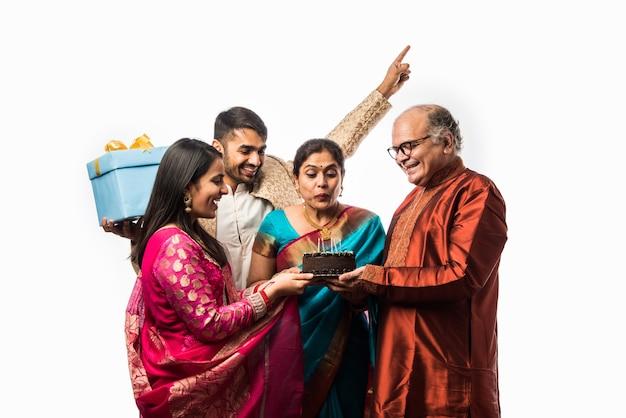 Indyjska starsza kobieta z rodziną świętującą urodziny, dmuchając świeczki na torcie, nosząc etniczne stroje