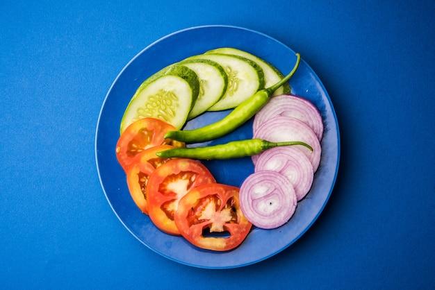 Indyjska świeża zielona sałatka w niebieskim talerzu ceramicznym