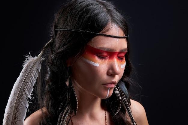Indyjska szamańska kobieta z indyjskimi piórami nosząca i kolorowy makijaż