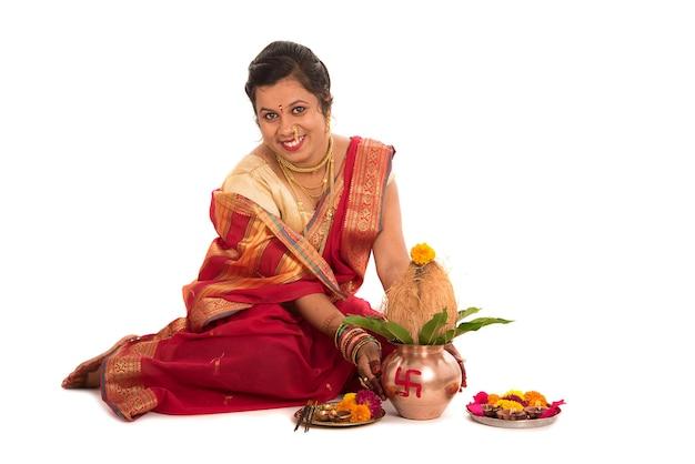 Indyjska tradycyjna kobieta wykonująca kult z miedzianą kalaszą