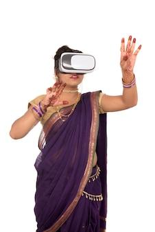 Indyjska tradycyjna młoda kobieta w sari, patrząc przez urządzenie vr