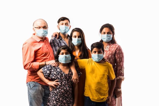 Indyjska wielopokoleniowa rodzina nosząca ochronną medyczną maskę na twarz podczas epidemii koronawirusa i grypy. na białym tle nad białą ścianą