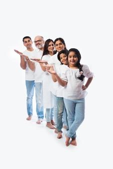 Indyjska wielopokoleniowa rodzina wskazująca lub prezentująca pustą przestrzeń, stojąca odizolowana od białej ściany