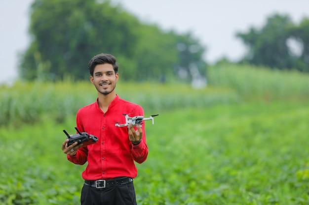 Indyjski agronom trzymając w ręku drona i pilota w dziedzinie rolnictwa