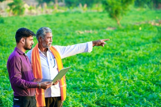 Indyjski agronom z rolnikiem w polu