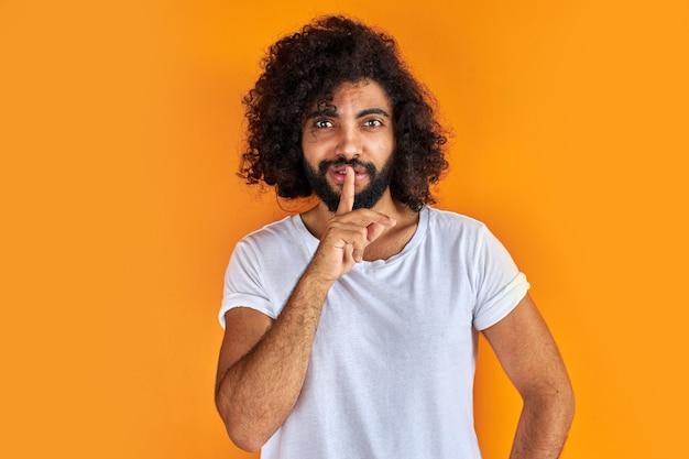Indyjski arabski mężczyzna prosi o spokój z palcem na ustach