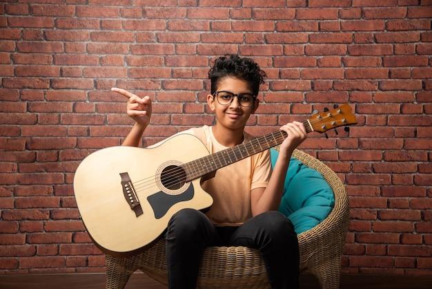 Indyjski azjatycki chłopiec grający na gitarze akustycznej siedząc przy białej ścianie