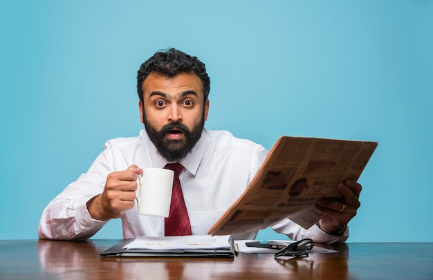 Indyjski azjatycki młody biznesmen czyta gazetę przy kawie przy biurku