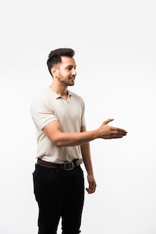 Indyjski azjatycki młody mężczyzna dający lub oferujący drżenie ręki, stojący na białym tle nad białym tłem