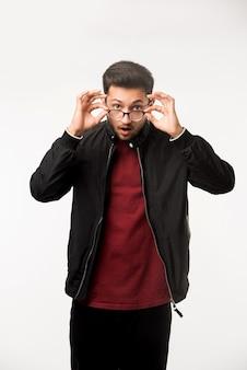 Indyjski azjatycki młody mężczyzna trzymający okulary lub okulary stojąc na białym tle