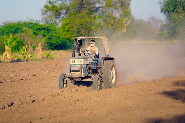 Indyjski / azjatycki rolnik z traktorem przygotowującym ziemię do siewu za pomocą kultywatora, indyjska scena rolnicza