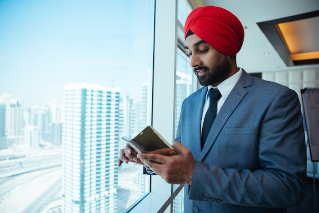 Indyjski biznesmen patrząc przez okno w jego biurze