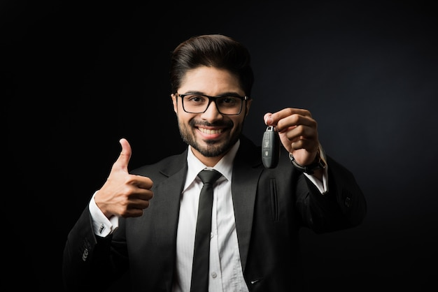 Indyjski biznesmen z kluczykami do samochodu, stojący odizolowany na czarnym tle