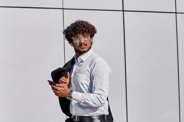 Indyjski biznesmen z kręconymi włosami w garniturze spaceruje po biurze