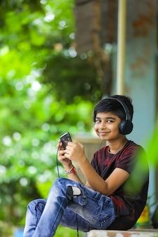 Indyjski chłopiec słuchania muzyki lub uczenia się na telefonie komórkowym