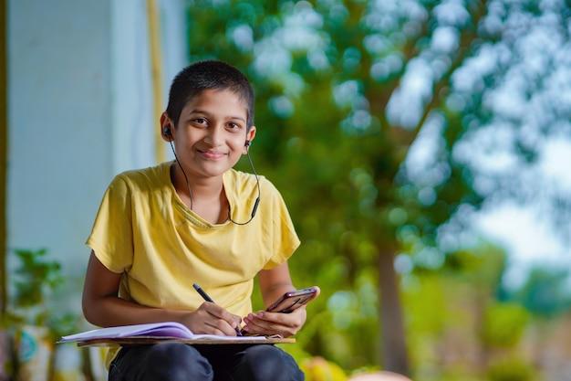 Indyjski chłopiec trzyma lekcję na odległość przez telefon za pomocą aplikacji mobilnej, ogląda lekcje online, rozmowy wideo w aplikacji, robi notatki, ucząc się w domu