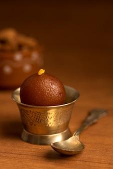 Indyjski deser lub danie słodkie: gulab jamun w miedzianej antycznej misce z łyżeczką