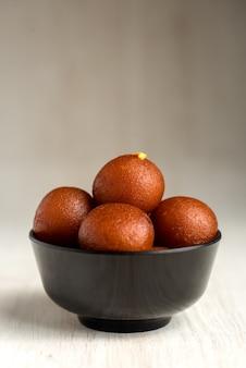 Indyjski deser lub słodkie danie: gulab jamun w misce na drewniane tła.