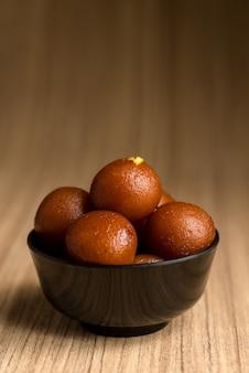 Indyjski deser lub słodkie danie: gulab jamun w misce na drewnianym stole.