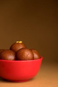 Indyjski deser lub słodkie danie gulab jamun w misce w ciemności.