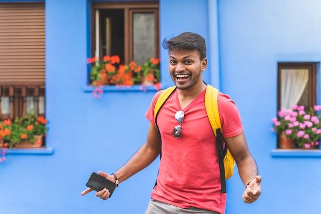 Indyjski facet uśmiecha się do kamery na niebieskim tle.