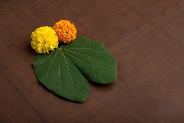 Indyjski festiwal dasera, pokazując złoty liść (bauhinia racemosa) i kwiaty nagietka na brązowym tle.