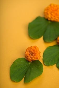 Indyjski festiwal dasera, pokazujący złoty liść (bauhinia racemosa) i kwiaty nagietka na żółtym stole.