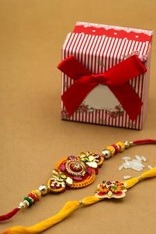 Indyjski festiwal rakhi, ziarna ryżu i pudełko na pomarańczowym tle