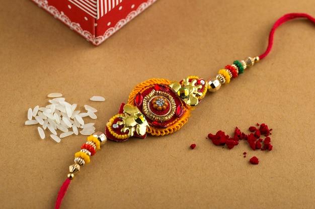 Indyjski festiwal raksha bandhan tło z eleganckim rakhi, ziarnami ryżu i pudełkiem prezentowym