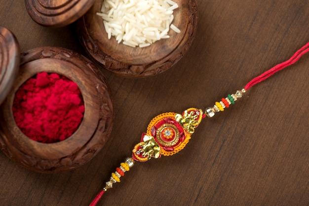 Indyjski festiwal: tło raksha bandhan z eleganckim rakhi, ziarnami ryżu i kumkum