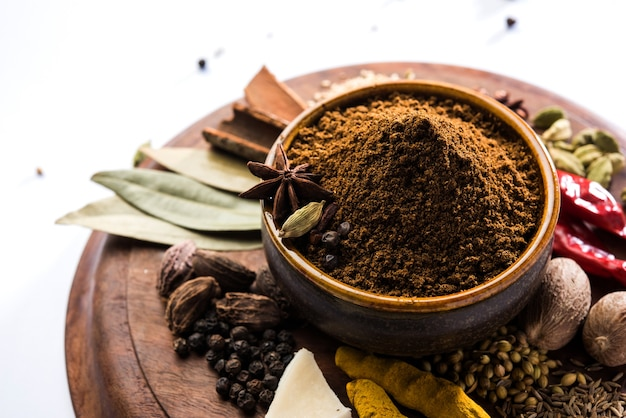 Indyjski garam masala w proszku w misce i jego składniki kolorowe przyprawy. podawane na nastrojowym tle. selektywne skupienie