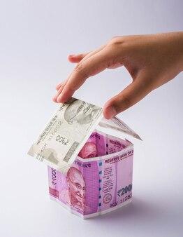 Indyjski koncepcja biznesowa nieruchomości przedstawiająca model 3d domu wykonane przy użyciu banknotów papierowych, izolowany nad kolorowym tłem. selektywne skupienie