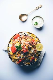 Indyjski kurczak tikka biriyani podawany w misce z jogurtem. selektywne skupienie