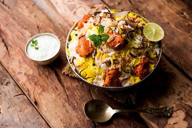 Indyjski kurczak tikka biriyani podawany w misce z jogurtem