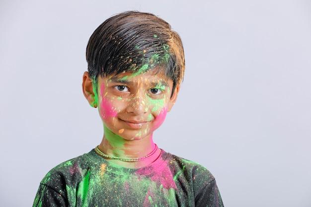 Indyjski mały chłopiec bawi się kolorem w festiwalu holi