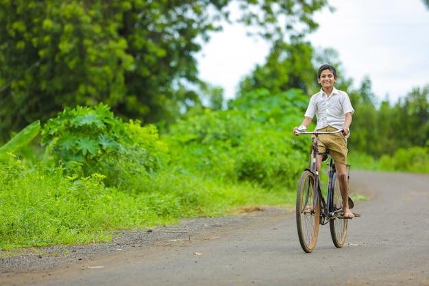 Indyjski mały chłopiec cieszyć się jazdą na rowerze