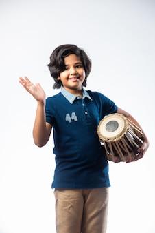 Indyjski mały chłopiec dziecko gra na instrumencie muzycznym tabla. to klasyczny instrument hinduski