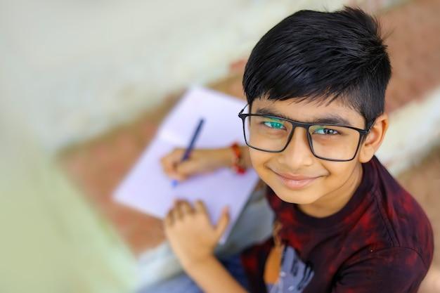 Indyjski mały chłopiec pisze na notatniku