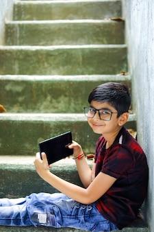 Indyjski mały chłopiec studiuje online przy użyciu telefonu komórkowego w domu