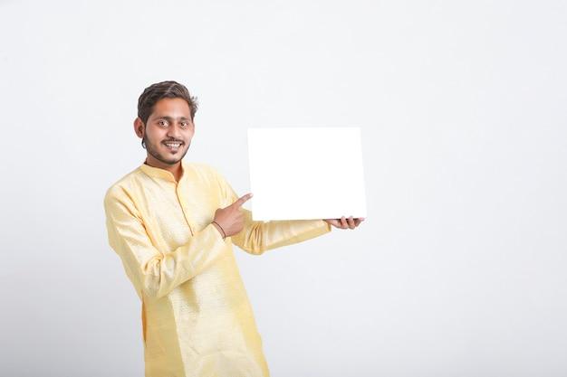 Indyjski mężczyzna trzyma białą tablicę stojącą nad białą ścianą