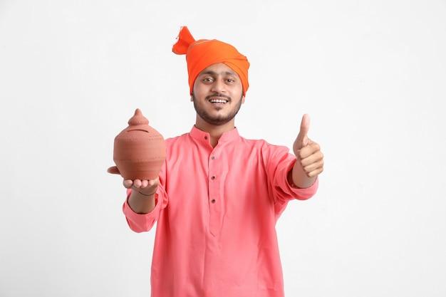 Indyjski mężczyzna trzyma skarbonkę na białej ścianie